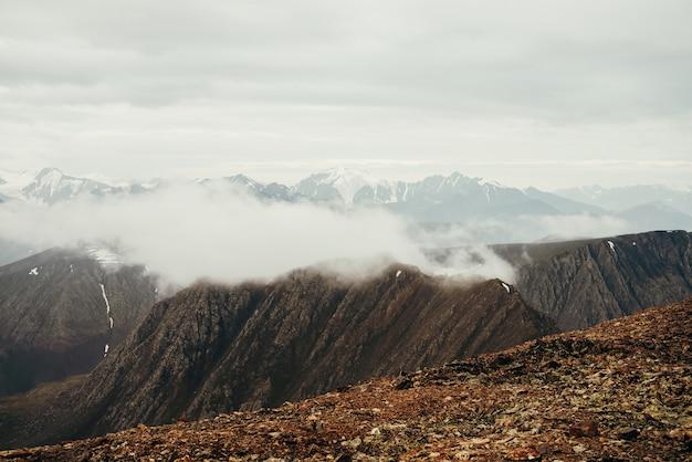 Atmosferico paesaggio alpino con grandi montagne rocciose e gigantesche montagne innevate con ghiacciaio