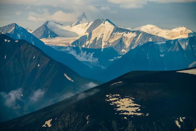 Atmosferico paesaggio alpino con grandi montagne innevate tra nuvole basse nell'ora d'oro. meraviglioso scenario dell'altopiano con neve splendente sul ghiacciaio sulla catena montuosa gigante all'alba. volando sopra le montagne.