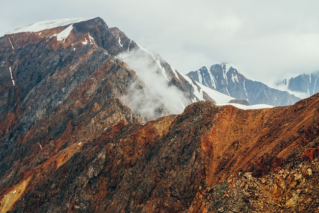 Atmosferico paesaggio alpino con nuvole basse sulle montagne rocciose rosse nell'ora d'oro. bellissima vista di grandi rocce arancioni e gigantesche montagne innevate con ghiacciaio all'alba. meraviglioso scenario dell'altopiano. parete rocciosa.