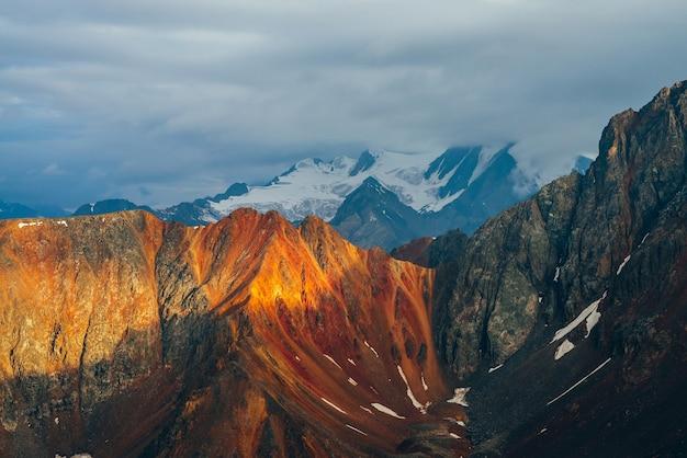 Atmosferico paesaggio alpino con montagne rocciose rosse nell'ora d'oro.