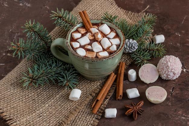 Composizione natalizia atmosferica, una tazza di cacao con marshmallow, biscotti di panpepato, dolci, cannella