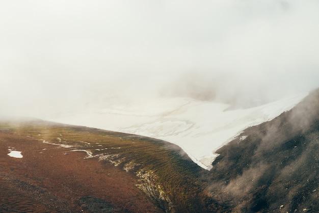 Atmosferico paesaggio alpino minimalista a valle dell'altopiano con ampio ghiacciaio sul pendio della montagna all'interno della nuvola. nuvole basse nella valle rocciosa. scenario montano tranquillo. splendida vista sulla montagna innevata