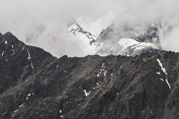 Atmosferico paesaggio alpino minimalista con grande parete rocciosa e picco innevato nelle nuvole basse