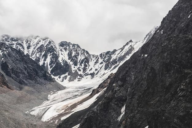 Atmosferico paesaggio alpino minimalista con un enorme ghiacciaio sospeso su una montagna gigante.