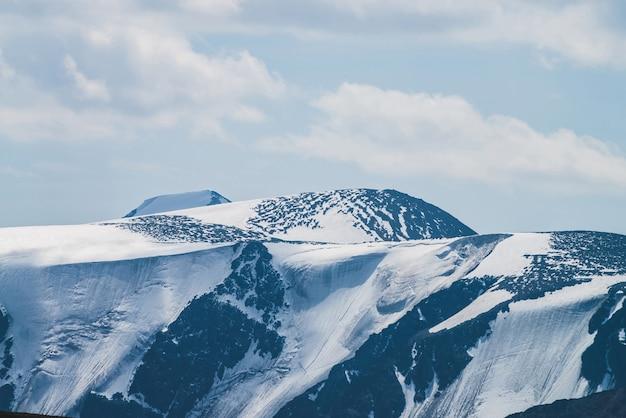 Atmosferico paesaggio alpino minimalista con massiccio ghiacciaio sospeso sulla cima della montagna innevata.