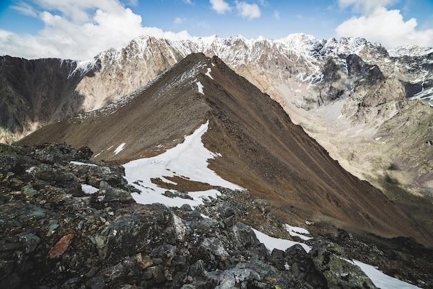 Atmosferico paesaggio alpino minimalista con massiccia catena montuosa innevata.