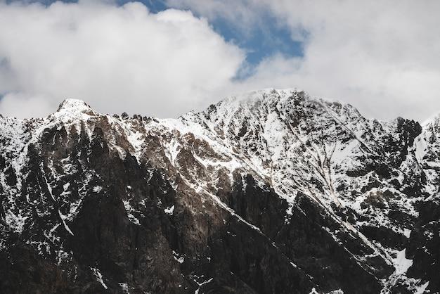 Atmosferico paesaggio alpino minimalista con picco di montagna rocciosa innevata