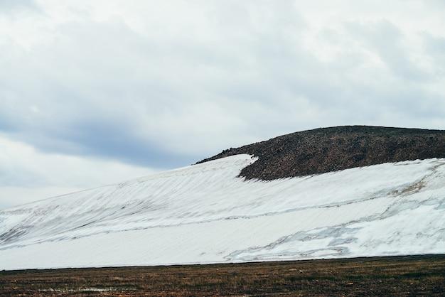 Atmosferico paesaggio alpino minimalista con ampio ghiacciaio sul pendio della montagna rocciosa sotto il cielo nuvoloso. meraviglioso scenario di montagna con montagne innevate nella valle dell'altopiano. colline rocciose con neve.