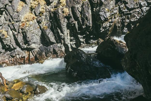 Paesaggio montano atmosferico con fiume di montagna turbolento tra rocce con muschio vicino a parete rocciosa al sole. bellissimo paesaggio alpino con pietre di muschio bagnate nel potente fiume di montagna alla luce del sole.