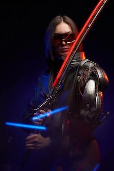 Ritratto atmosferico di una bellissima assassina femminile in posa su uno sfondo scuro con fumo. armato di spada incandescente donna militare con occhiali da sole e impianto.
