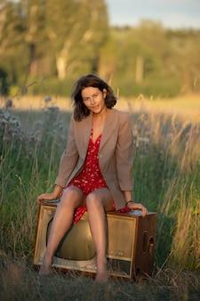 Atmosferico ritratto di una giovane donna in un abito rosso seduto su un vecchio televisore retrò in natura.