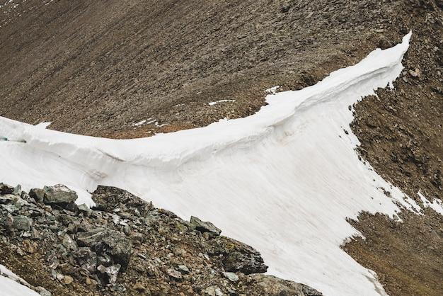 Paesaggio alpino minimalista strutturato atmosferico con firn o neve sulla cresta della montagna rocciosa del grande pettine. collina ghiaione innevata. roccia del torrente boulder. paesaggi maestosi in alta quota. Foto Premium
