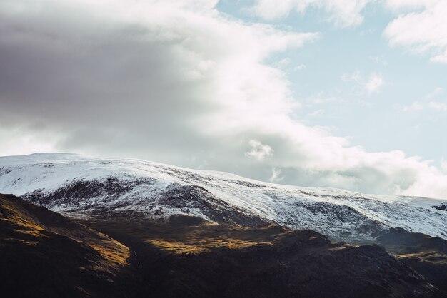 Vista atmosferica alle montagne innevate alla luce del sole sotto il cielo nuvoloso