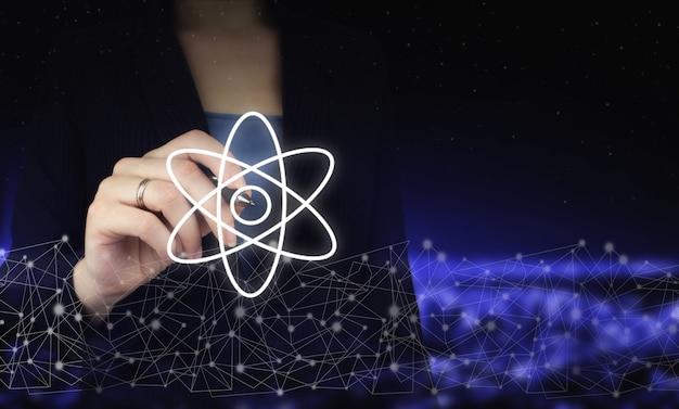 Estratto della molecola dell'atomo. mano che tiene la penna grafica digitale e disegna il segno dell'atomo della molecola dell'ologramma digitale sullo sfondo sfocato scuro della città. molecola dell'atomo come concetto per la scienza.