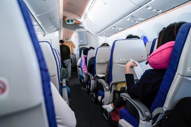 Presenza del passeggero che legge un libro nella fila del sedile dell'aereo.