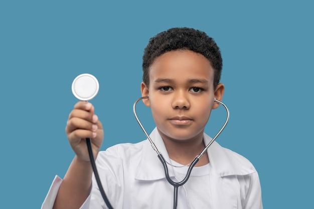 Attenzione, ascolto. fiducioso calmo ragazzo di età scolare dalla pelle scura in camice bianco con stetoscopio in ascolto