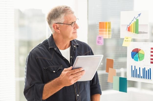 Uomo d'affari attento che guarda i diagrammi di flusso sulla parete