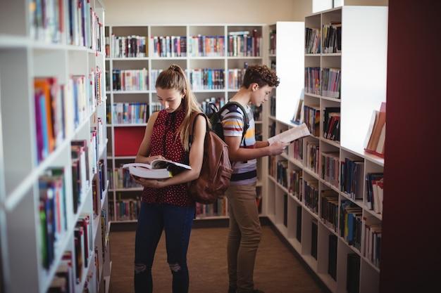 Compagni di classe attenti che leggono il libro in biblioteca
