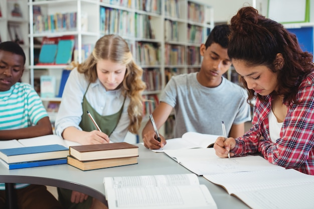 Compagni di classe attenti che studiano in biblioteca