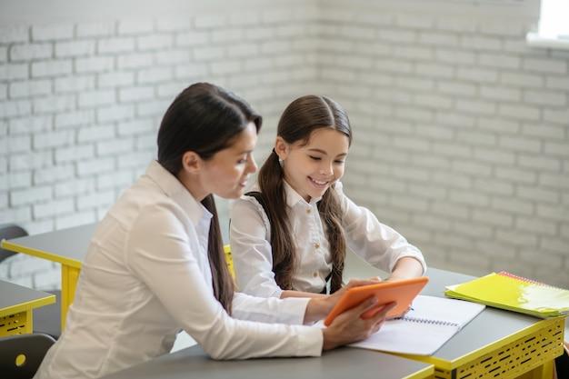Giovane insegnante gentile attento con tablet e studentessa felice seduto alla scrivania durante la lezione individuale