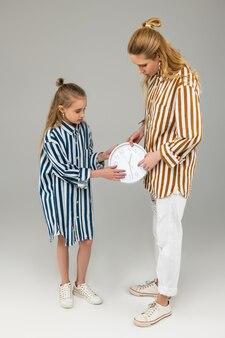 Attenta donna dai capelli lunghi in camicia arancione a righe che punta in tempo sull'orologio mentre lo porta con la sorellina