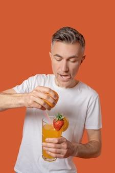 Uomo attento che spreme il succo d'arancia nel bicchiere
