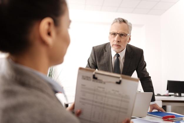 Uomo attento che indossa un costume intelligente e occhiali premendo le labbra mentre guarda la sua segretaria