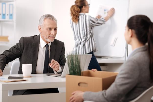 Impiegato attento che indossa camicia a righe in piedi al consiglio mentre fa il diagramma