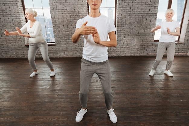 Ritiri attenti che mettono le gambe alla larghezza delle spalle mantenendo le braccia piegate sui gomiti seguendo il loro istruttore