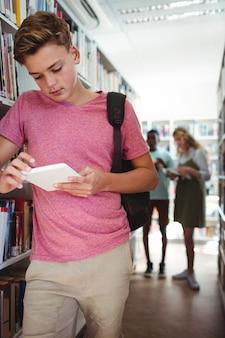 Scolaro attento utilizzando tavoletta digitale in biblioteca