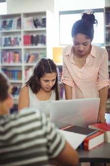 Studenti attenti che utilizzano laptop in libreria