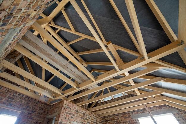 Locale sottotetto di un fabbricato in costruzione con travi in legno di una struttura di copertura e pareti in laterizio. concetto di sviluppo immobiliare.