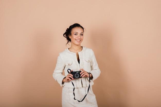 Attraente femmina nera afroamericana, utilizzando una fotocamera digitale slr scattare fotografie in studio. studente di fotografia e stile di vita turistico.
