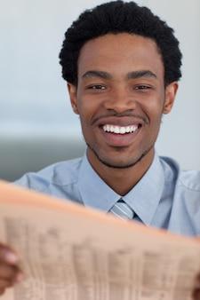 Uomo d'affari afroamericano attraente che legge un giornale