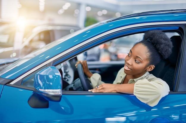 Attraente donna afro sogna un'auto nuova, giovane donna è venuta a vedere automobili, a fare acquisti.