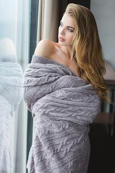 Attraente giovane donna seducente con bei capelli lunghi in coperta grigia che guarda attraverso la finestra