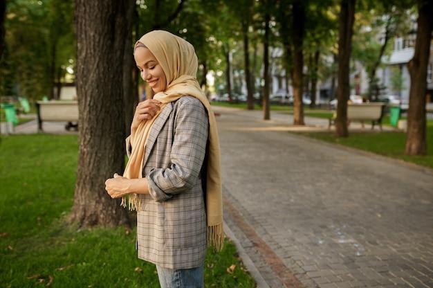 Attraente ragazza araba in hijab pone nel parco estivo. donna musulmana che riposa sul prato nel campus universitario.