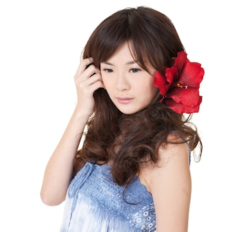 Attraente bellezza asiatica con espressione solitaria sul muro bianco.