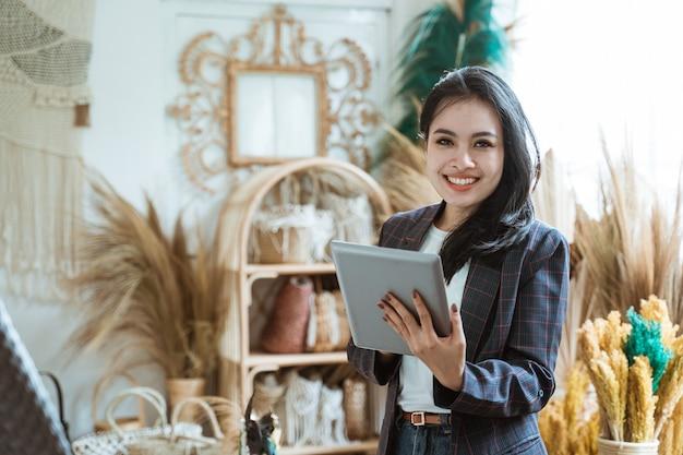 Attraente imprenditore asiatico presso il suo negozio di arte e artigianato che vende merci realizzate con prodotti naturali