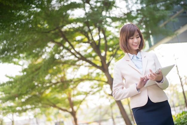 Donna asiatica attraente di affari che lavora al calcolatore del ridurre in pani fuori dell'ufficio