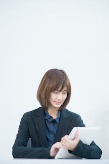 Donna asiatica attraente di affari che lavora al computer tablet nel posto di lavoro