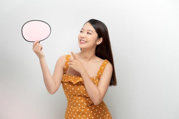 Attraente femmina asiatica con messaggio vuoto isolato su sfondo bianco.