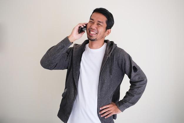 Attraente uomo asiatico che sorride felice mentre chiama qualcuno con la mano sulla vita