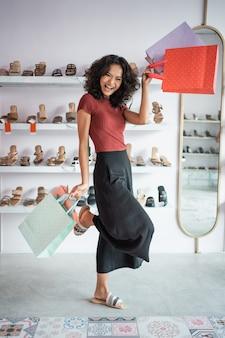 Donna asiatica attraente di acquisto con il sacco di carta