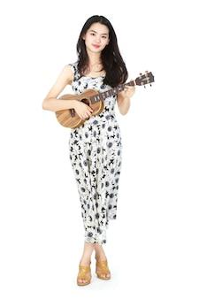 Donna asiatica attraente che gioca ukulele