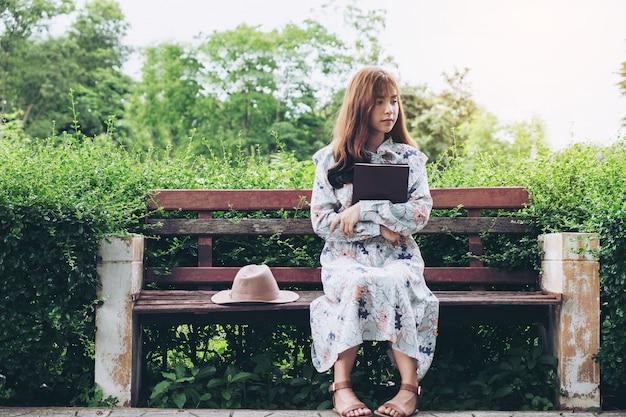 Attraente donna asiatica leggendo un libro e rilassante al parco