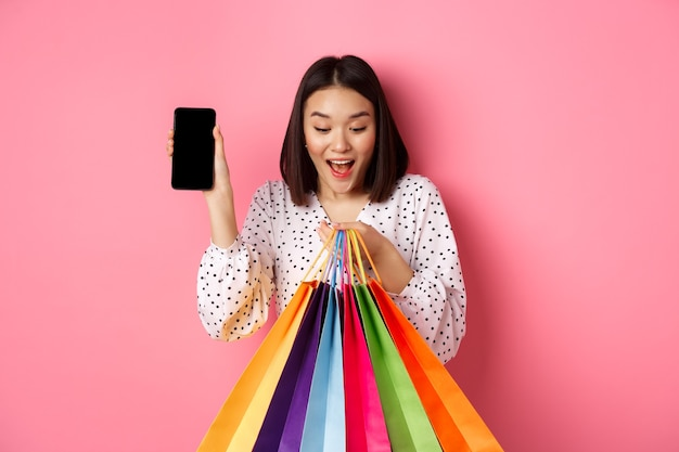 Attraente donna asiatica che mostra app per smartphone e borse della spesa, acquisti online tramite applicazione, in piedi sopra il rosa