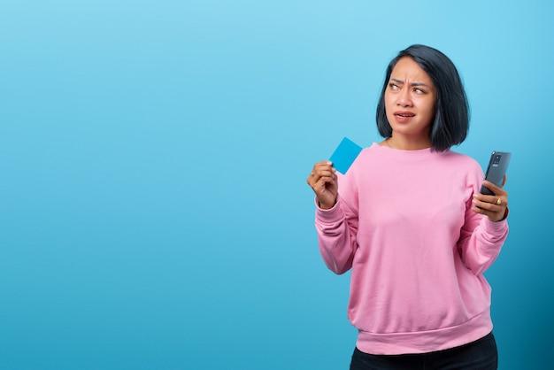 Attraente donna asiatica che pensa e cerca lo spazio vuoto su sfondo blu