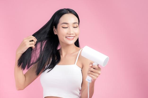 Attraente donna asiatica usinf asciugacapelli sul rosa.