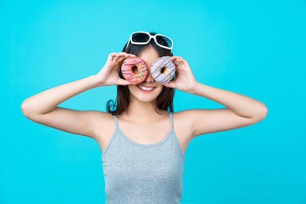 La giovane donna asiatica attraente che gioca con le ciambelle sulla parete blu isolata di colore, la perdita di peso ed evita gli alimenti industriali per essere a dieta e il concetto sano